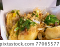 Big takoyaki, a close up of Japanese delicious fried octopus balls food in white paper box at Taipei night market, Taiwan. 77065577