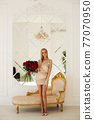 Gorgeous blonde model with red roses bouquet. 77070950