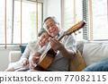 Asian senior Couple enjoying singing and playing acoustic guitar 77082115