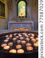 Many burning candles in church. Selective focus 77087029