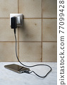 A cell phone charging 77099428