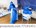 Heathcare worker in full personal protection equipment managing outdoor covid-19 testing center 77101451