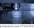 3D printer prints bkue gray form figure close 77101454
