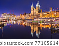 Amsterdam, Netherlands city center view with riverboats and the  Basilica of Saint Nicholas 77105914