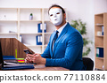 Young male employee wearing mask in the office 77110884