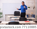 Young male teacher in front of whiteboard 77110885
