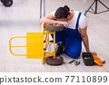 Young male repairman repairing trolley indoors 77110899