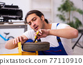 Young male repairman repairing trolley indoors 77110910