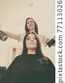 Hairdresser drying dark female hair using professional hairdryer 77113026