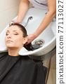 Hairdresser washing her woman customer hair 77113027