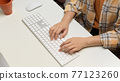 Female freelancer hands typing on computer keyboard on white table in home office room 77123260