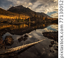 Sunrise at lake in mountain range. Beautiful reflection of clouds in water 77130052