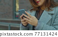 Close up female holding smartphone mobile device, uses chat with friends abroad or family to communicate. Woman with smartphone in hands. 77131424