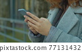 Close-up of woman typing on phone. Business woman uses smartphone on street. Modern touch-sensitive smartphone in hands of young woman. Social media. Work. Business. Relax. 77131432