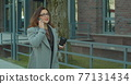 Woman in the glasses goes near business center with documents and talks on the phone. Successful female executive at work. 77131434