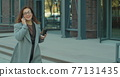 Woman in the glasses goes near business center with documents and talks on the phone. Successful female executive at work. 77131435