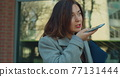 Businesswoman sending audio voice message on smartphone near modern office building talking to mobile assistant. Businesswoman using telephone. 77131444