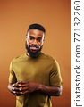 young pretty african american man posing cheerful on brown background, lifestyle people concept 77132260
