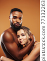 Young pretty couple diverse races together posing sensitive on brown background, lifestyle people concept 77132263