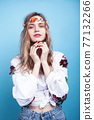 young pretty blond girl posing on blue background, fashion style hippie boho flowers on head 77132266