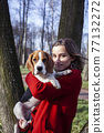 pretty young girl in red coat playing with dog outside in green park, lifestyle people concept 77132272
