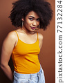 pretty young african american woman with curly hair posing cheerful gesturing on brown background, lifestyle people concept 77132284