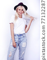 young pretty blond girl hipster in hat on white background casual close up dreaming smiling posing cheerful, lifestyle people concept 77132287