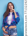 young pretty girl posing happy smiling on blue background, lifestyle people on summer vacation concept 77132292