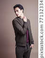 young pretty asian man posing in fashion style on light brown background, lifestyle people concept 77132334