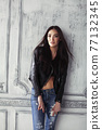 young brunette woman in leather jacket at vintage wall 77132345