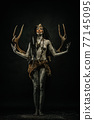 Tribal shaman covered in clay, wearing dreadlocks, bone necklaces and deer antlers on their backs 77145095