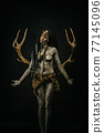 Tribal shaman covered in clay, wearing dreadlocks, bone necklaces and deer antlers on their backs 77145096