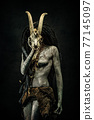 Portrait of a shaman covered in clay, wearing dreadlocks, bone necklaces holding a goat head skeleton 77145097