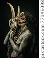 Portrait of a shaman covered in clay, wearing dreadlocks, bone necklaces holding a goat head skeleton 77145098