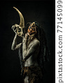 Portrait of a shaman covered in clay, wearing dreadlocks, bone necklaces holding a goat head skeleton 77145099