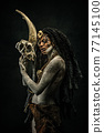 Portrait of a shaman covered in clay, wearing dreadlocks, bone necklaces holding a goat head skeleton 77145100