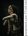 Portrait of a shaman covered in clay, wearing dreadlocks and bone necklaces 77145102