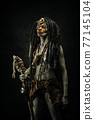 Tribal shaman covered in clay, wearing dreadlocks, bone necklaces and a scepter 77145104