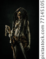 Tribal shaman covered in clay, wearing dreadlocks, bone necklaces and a scepter 77145105