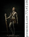Tribal shaman covered in clay, wearing dreadlocks, bone necklaces and a scepter 77145106