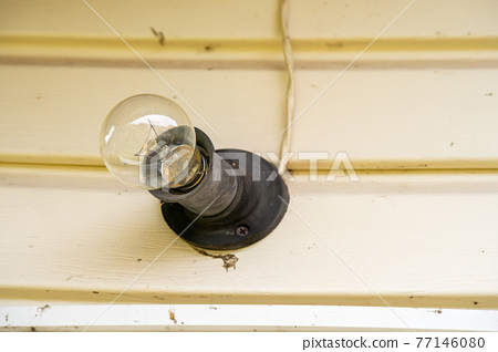 An incandescent light bulb with cobwebs and dirt illuminates the white wall in the entrance of the house. The beginning of the summer cottage season 77146080