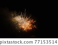 Colored fireworks explode in the dark night sky 77153514