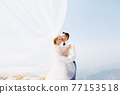 The bride and groom are embracing on the mountain, the groom kisses the bride, the wind waves the veil  77153518