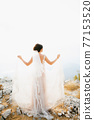 The bride stands on the rocks with her arms outstretched, behind her, a thin fabric of skirts flutters in the wind, back view  77153520