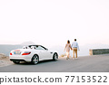 Man and woman holding hands are walking along the road against the background of a white expensive sports convertible 77153522