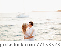 The bride and groom are embracing on the seashore and are about to kiss, a white yacht sails behind them 77153523