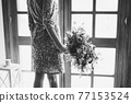 A bride in an unusual dress with sequins stands at the balcony door and holds a wedding bouquet, black and white photo 77153524