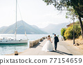 The bride and groom are walking hand in hand on the road by the sea, a white yacht is standing near the shore  77154659