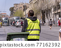Jerusalem, Israel, November 14, 2020 : A municipal worker in a reflective vest sits, rests and looks at messages on a mobile phone on the Muristan Street in the old city of Jerusalem in Israel 77162392