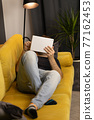 No face guy chatting and messaging via tablet online lying sofa in stylish room 77162453